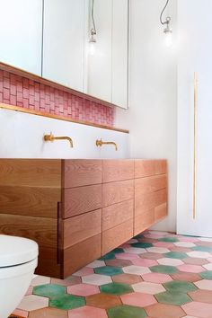 Pink + White + Wood Bathroom - Colorful hexagon floor tile - Pink backsplash - White upper cabinets, wood lowers - Brass fixtures