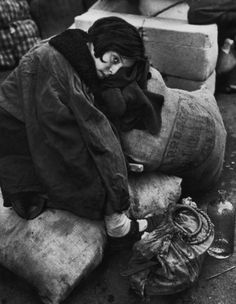 Robert Capa; Little girl resting during the evacuation of the city, Barcelona, 1939