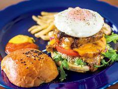 《 池尻大橋 》「ルリイロバーガー」¥1,500。(前菜、コーヒー付き)スモーキーな肉とソース、具材のバランスが完璧!  丁寧な手仕事が光る、美ジュアル系バーガー  『+ruli-ro』  池尻大橋  炭火で焼いた豪快な肉料理に定評のある『ルリイロ』に土日のランチ限定でハンバーガーが登場。フレンチやイタリアンのエッセンスを加えたスカルモッツァチーズバーガー、ラタトゥイユバーガーなどオリジナリティが光る12種のバーガーのなかでもイチオシは、国産牛挽肉100%のパティに自家製ベーコンやフライドエッグを盛りこんだ「ルリイロバーガー」。   バターと卵をたっぷり使った自家製バンズが炭の香りをまとった肉の旨みを丸ごとホールド。レストランならではの卓越した味わいに心を掴まれる。