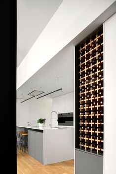 A modern kitchen with built-in wine storage. Luz Natural, Agi Architects, Wood Facade, Wine Rack Storage, Wood Wine Racks, White Countertops, Smooth Walls, Wood Slats, Facade House