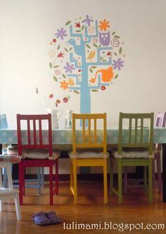 Zona pranzo. Albero dipinto sulla parete e sedie colorate.