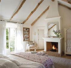 Exposed beams, built in bookshelves, fireplace, white decor. I literally cannot find something I do not like in this room.