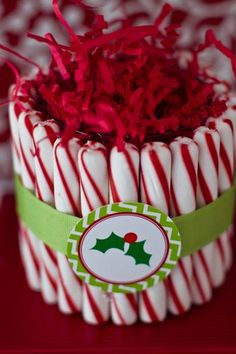 - We glued old fashioned peppermint sticks around a low ball glass as a display at the top center of the dessert table, and adorned it with a coordinating logo from the printable collection.