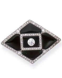 AN ART DECO DIAMOND AND ONYX BROOCH, BY SHREVE  CO.  The kite-shaped brooch, composed of geometric onyx plaques, centering upon an old European-cut diamond, enhanced by old European and single-cut diamond detail and trim, mounted in platinum, circa 1925 Signed Shreve and Co.