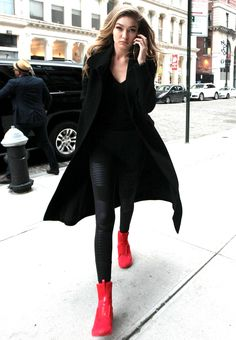 Gigi Hadid accented her all-black ensemble with a pair of Rihanna's sold-out red Fenty x Puma sneakers.