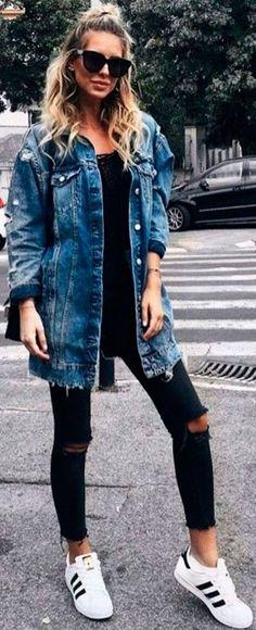 Look de inverno com jeans preto destroyed, blusa preta, jaqueta jeans oversized e tênis branco.