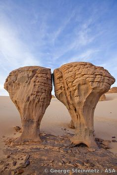 WIND-ERODED STONES, LIKE A PAIR OF MOLARS WITH THEIR CONNECTIVE TISSUE STRIPPED AWAY, EMERGE FROM THE SANDS NEAR INAKASHAKER (NAMED AFTER A KIND OF LOCALLY-FOUND BUSH IN TUAREG LANGUAGE). THIS IS AN AREA OF BEAUTIFULLY ERODED ROCK FIVE HOURS DRIVE SE OF TAMANRASSET, IN THE TASSILI DU HOGGAR.