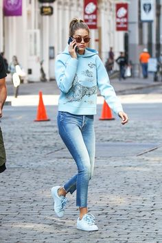 Gigi Hadid wears a graphic hoodie, jeans, blue Puma sneakers, and round sunglasses