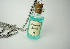 """2ml glass vial filled with shimmery blue-green """"mermaid tears."""" Bottle measures 35mm x 16mm (1.38 in x 0.63 in) and comes on 18"""" silver ball-chain. Bottle cork will be secured in place with waterproof sealant to prevent leakage and/or cork damage. All contents are non-toxic but bottles are ..."""