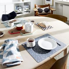 A pair of grey placemats by OYOY featuring a mini triangle print in grey and white. With the minimalist yet fun design, these placemats make a