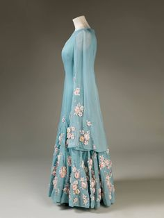 This blue silk and silk chiffon dress by Norman Hartnell has long draped sleeves and a flared panelled skirt which are embroidered with sprays of cherry blossom, the national flower of Japan. Her Majesty The Queen wore the dress for a State Visit to Japan in 1975.