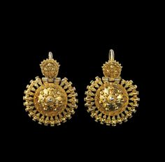 Pair of gilded silver bow earrings with granulate decoration and a disc jointed by hinge to the bow. 16th century A.D.