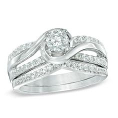 Polished and diamond-lined ribbons sweep and swirl around the center stone, wrapping it in a sparkling embrace and creating the ring's gracefully bypassing shank.