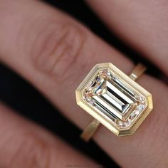 An incredible custom emerald cut diamond engagement ring by Erika Winters!! I love the yellow gold bezel setting.