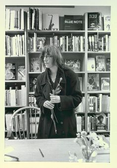 Patti Smith holding flowers in front of jazz books in bookstore Photo by Allen Ginsberg, 1995.