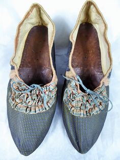 Pair of woman's shoes, France, c. 1770-1790. Blue and green figured silk taffeta, tricolor-coloured silk ribbon trim, white leather covered heels.