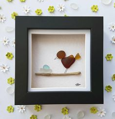 Adorable and original sea glass art picture of a red, brown and yellow sea glass bird standing on a driftwood branch lovingly overlooking their beautiful light blue sea glass egg in a white sea glass nest. The sea glass art is part of the new miniature frame collection and comes in a cute