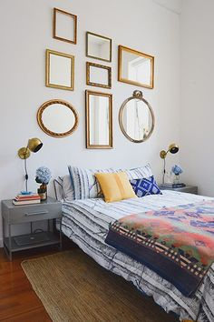 Revamp Your Apartment For Zero Dollars #refinery29 http://www.refinery29.com/unique-ways-declutter-apartment#slide5 These mirrors of different shapes and sizes (but similar shades of gold) draw the eyes to the area above the bed. And, if your bed is simple, like this one with no headboard, decorating around it can help revamp your bedroom quickly.Related: Would A Homemade Headboard Completely Change The Look Of Your Bedroom?