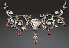 An Antique Diamond And Ruby Necklace  The front with central triangular old mine-cut diamond within rose-cut diamond surround suspending an articulated ruby and diamond line to the scrolled sides and link backchain, to a closed back, mounted in silver and gold, circa 1890
