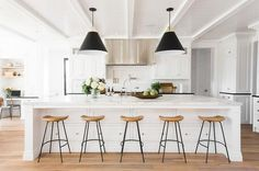 Five sleek wood and island counter stools sit in front of a large white island fitted with stacked drawers donning polished nickel knobs and a white marble countertop finished with a sink and polished nickel gooseneck deck mount faucet illuminated by two eye-catching Rejuvenation Butte Cone Pendants hung from a beadboard ceiling accented with white beams.