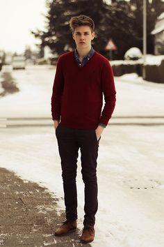 Él lleva un suéter rojo, pantalones negros, y zapatos marrón. El suéter Cuesta ochenta dólares, los pantalones cuestan cuarenta dólares, y los zapatos cuestan ciento veinte dolares