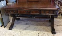 Lion's paw feet on fluted curule legs and other hand carved details make this a writing desk fit for an emperor. Tooled leather top, 3 drawers, generous proportions. SOLD
