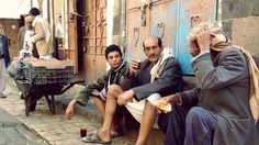 """Three men sit in the old city of Sanaa on April 19, 2015. """"œWe are enjoying our cup of tea under the melody of those stupid jets hovering all over,"""" one says."""