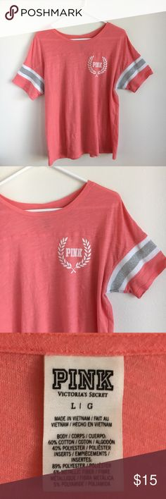 Coral VS PINK Tee This lightweight, coral colored PINK tee with silver and white sleeve details will be the perfect addition to your Victoria's Secret collection. Size large, fits loose. Pair with your favorite VS leggings! Great condition. PINK Victoria's Secret Tops Tees - Short Sleeve