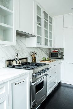 white kitchen, shaker cabinets with mix of closed and glass doors, like the handles, great low profile range hood, omit marble counters / Greenwich Village Apartment by Katie Martinez