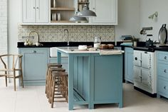 """We can picture this kitchen in a chic French château - the pale blues, creams and greys, the rustic wooden stools and, our favourite touch, those oh so pretty tiles used as a splashback.   [link url=""""http://www.firedearth.com""""]Fired Earth[/link]  [link url=""""http://www.houseandgarden.co.uk/homes/flower-arranging-flower-arrangement-tips""""]Unique ways to display fresh flowers[/link]"""