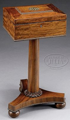 """FINE REGENCY INLAID MAHOGANY TEAPOY.  First quarter 19th century, England. The rectangular mansard hinged top with central contrasting star inlay opening to an interior fitted with a pair of cylindrical compartments with molded lids flanked by a pair of hinged covered caddies raised on a cylindrical pedestal with conforming reeded foot on a tripartite base with spool molding raised on ball feet. SIZE: 31"""" h x 15"""" w x 12"""" d."""