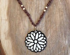 """Add a little earthy-chic to your collection with this elegant, handmade Mandala flower hemp necklace! A lightweight painted wood mandala flower pendant hangs on a 20"""" hemp macrame necklace with matching wood accent beads. The mandala flower pendant measures 2"""" in diameter. The mandala hemp necklace necklace hangs loosely and comfortably on the neck, is one of a kind, and closes with a silver lobster claw clasp."""