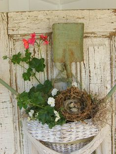 Create a welcoming entrance with a rustic basket. Use a bird's nest, garden tool & summer blooms.