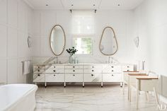 Complementary mirrors by India Mahdavi hang above a Connecticut master bath's custom-made double vanity, which is sheathed in marble and equipped with drawer pulls by Ted Muehling for E. R. Butler & Co.