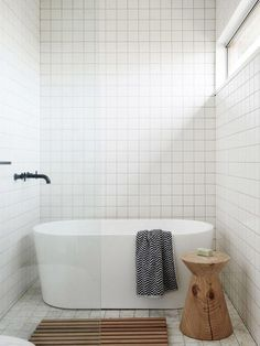 A contemporary and minimalist master bathroom with floor to ceiling square white porcelain tiles with light gray grout, black floating wall-mounted faucet, freestanding straight up modern soaking bathtub, chevron striped Turkish fouta towel, and carved solid wood side stool. See more interior design inspiration, ideas and work by Jeff and Mariko Provan on The Design Files.