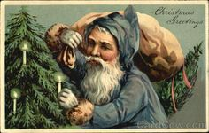 Santa in blue robe placing candle on tree Christmas Greetings