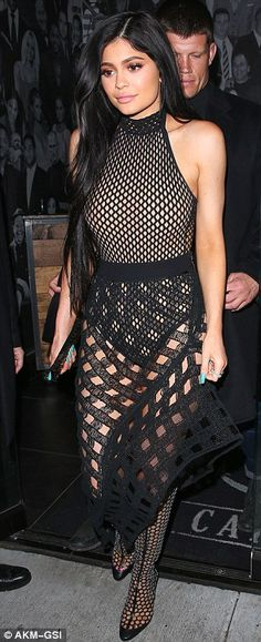 Oh my cod: Showcasing plenty of leg, she worked a black fishnet detailed halterneck bodysuit which skimmed her honed waist while teasing at her decolletage and shoulders