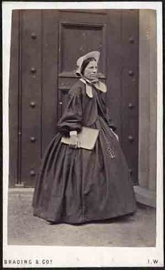 "Circa 1850 Outdoor portrait of a housekeeper. She stands, before a large door, in her dress, matching jacket and bonnet, holding a ledger book in one hand, and with two large keys suspended from chains, prominently displayed on the front of her skirt. Studio and backmark of ""Brading & Co., Newport, Isle of Wight""."