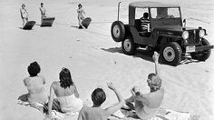 Sunbathers on a beach near Southampton, NY, greet a trio of surfers pulled along the beach by an all-terrain vehicle in 1955.