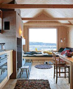 ENORM UTSIKT: Fra stue/kjøkken-sonen er det fri sikt over Yddin og Valdres-viddene. Det store stuevinduet i sørveggen oppleves som et maleri. Tepper og puter fra HAY. Sitte/ligge-sone mot utsikten. Foto: Espen Grønli