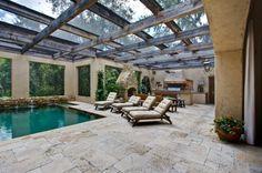 O teto de madeira e vidro valoriza a luz natural e traz um clima rústico ao espaço da piscina