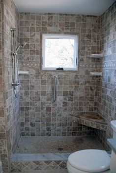 Tiled shower stall with corner bench and window.