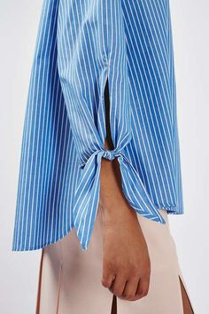 Leave shoulders bare in this oversized off-the-shoulder blouse. Finished with a striped pattern and tie detail to the sleeves, opt for clean lines on your bottom half for on-trend chic. #Topshop