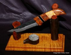 Display hunting knife in stand. Blade by famed Japanese blademaker, Saji. Decorative handle of Hawaiian koa, mango and buffalo horn. Koa and Ohia stand. We enjoy making custom requests and will also put a new handle on your favorite knife. www.SalterFineCutlery.com