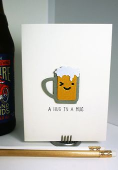 Do you know someone whos had a rough week? This fun card features a winking beer mug with the hand-stamped sentiment, A hug in a mug. Whether its a birthday, a celebration of a new job or just another day in the life, this blank note card will be well-received.  This card design is created with hand-stamped ink, die cuts and layered paper to give it a unique look. A2 sized ivory card (5.5 x 4 inches) includes a matching ivory paper envelope. Card is packaged in a clear cellophane resealable…