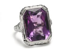 Art Deco ring of impressive proportion and magnificent deep medium coloration. Imagine an emerald cut natural amethyst of more than 15 by 11 mm in size and a weight greater than 9 carats. Set in a classic octagonal shaped mount of 14k white filigree gold. Superb…dramatic…and yours.    Date: Circa 1930. by millie