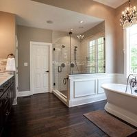 Free standing pedestal bath, glass shower with one side trimmed and wood tile floors