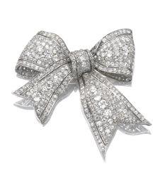 Diamond brooch, Early 20th Century. Of ribbon bow design, pavé-set with circular-, cushion- and single-cut diamonds.