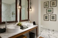 Unique, contemporary bathroom design in white marble, with vessel sinks and pendant lighting.