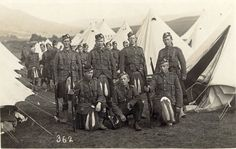Soldiers of the 5th Seaforth Highlanders in front of white bell tents at summer camp. 1914-1918